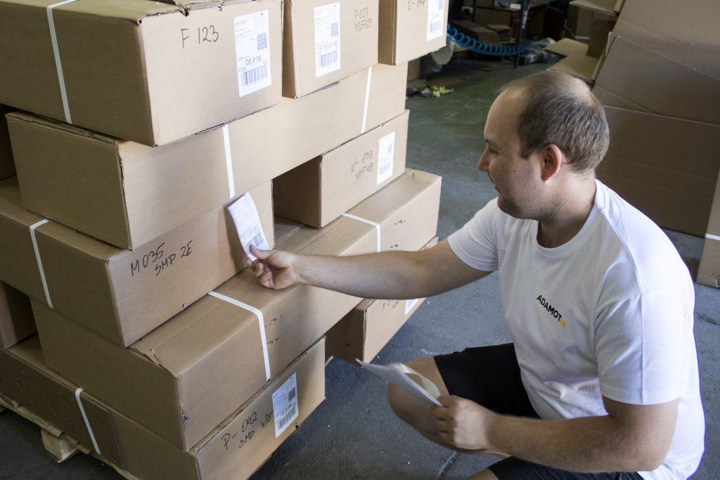 Pracownik magazynu precyzyjnie adresuje paczki z hakami holowniczymi.