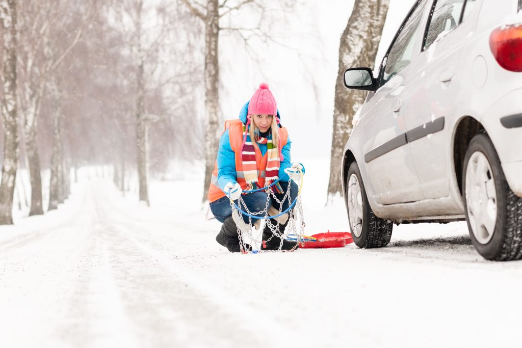 Montaż łańcuchów śniegowych. Poobcze zaśnieżonej i oblodzonej drogi
