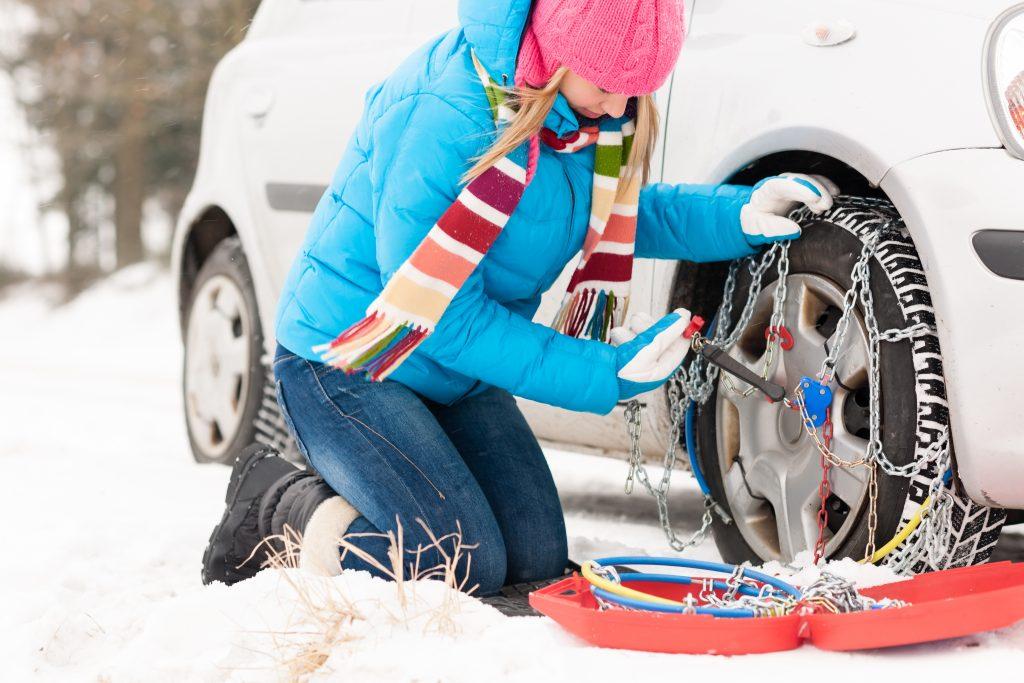 Samodzielny montaż łańcuchów śniegowych na poboczu zaśnieżonej i oblodzonej drogi.